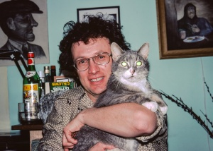 "Carl in his basement apartment surrounded by his drawings and hugging Puff: one of his long lived cats. Carl was a good friend for most of my adult life. During the many years I lived in Edmonton I spent a lot of time with Carl. It's rather odd that I have so few pictures of him. I have been an avid amateur photographer since I was eight but I only have half-a-dozen pictures of Carl. I held off ""developing"" this image because of the reflection in Puff's eyes. Now I see this informal imperfection as a reflection, (pun intended), of Carl's haphazard fun filled way of life."